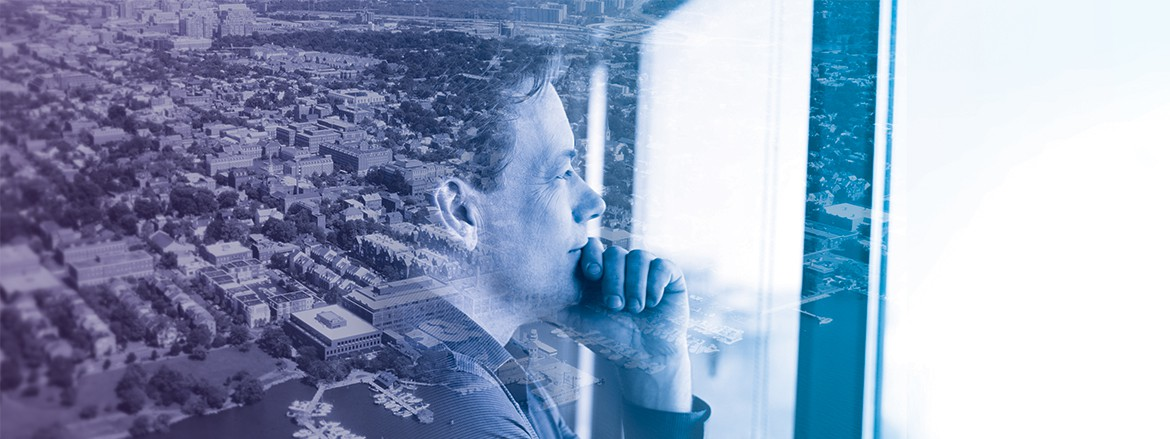 Profile of man looking out of a window, a city can be seen behind him