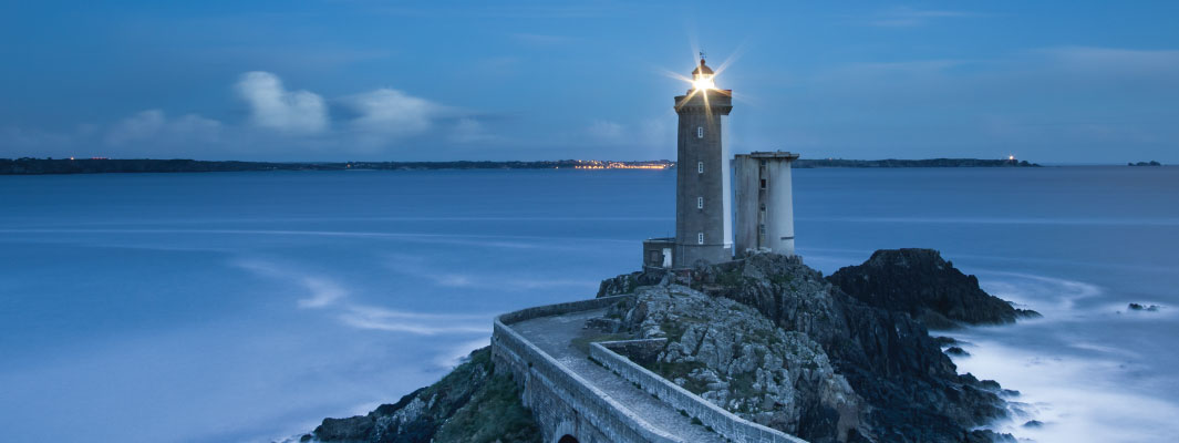 Photo of a lit lighthouse at twilight.