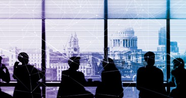 Photo of office buildings through a conference room window. Silhouetted business people are having a meeting in the room.